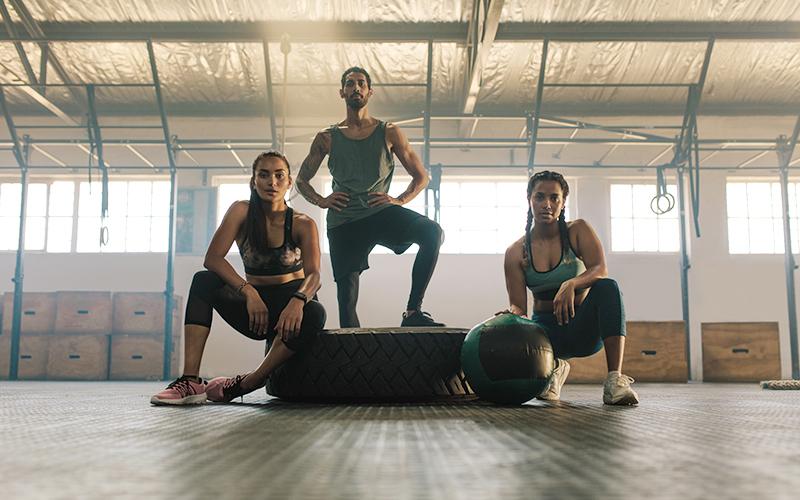 home et femmes prêts à faire du sport dans un gymnase