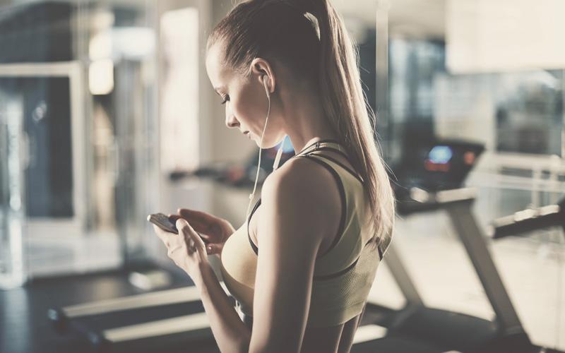 Sportlerin im Fitness-Studio wählt Musik auf ihrem Handy aus.