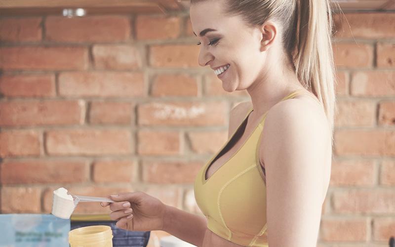 Frau mit gelbem Top trinkt Protein Shake