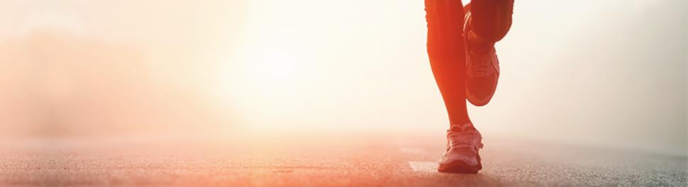 Füße in Sportschuhen und Laufschritt auf asphaltierter Straße im Morgenrot