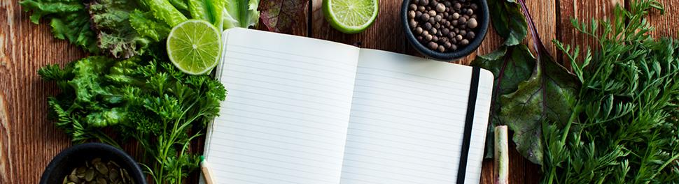 Aufgeschlagenes Notizbuch und grüne Gemüse auf Tisch