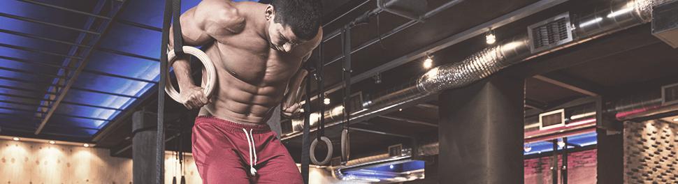 Muskulöser Mann trainiert an den Ringen im Fitnessstudio