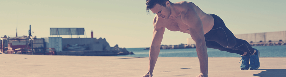 Muskulöser Mann macht Liegestütze am Hafen
