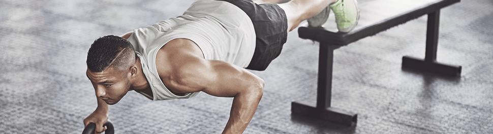 Ein Mann macht raised push-ups mit Kettlebells