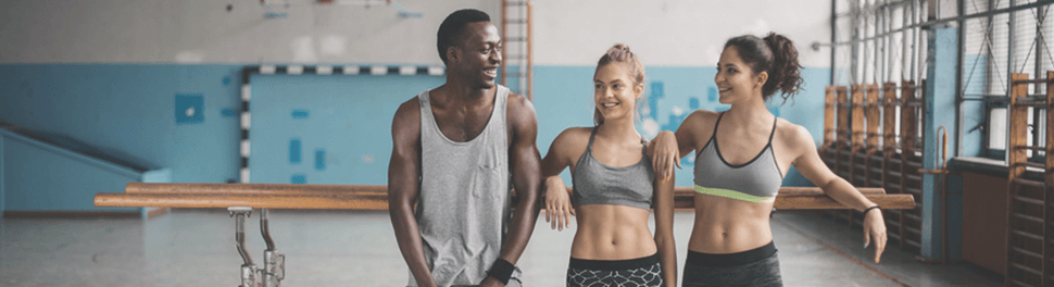 A dark-skinned man and two women standing in a gym