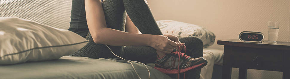 Athlete sitting on her bed, lacing her running shoes