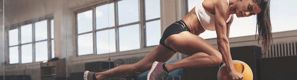 athletische Frau führt Bauchübung mit Ball aus