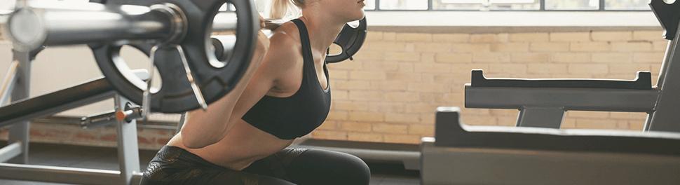 Frau beim Krafttraining mit Gewichtstange