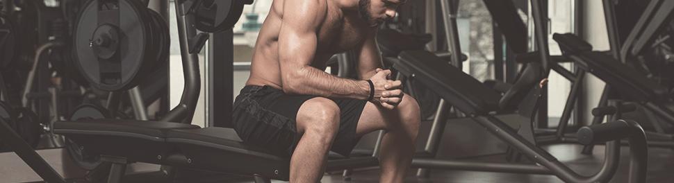 Muskulöser Mann sitzt im Fitnessstudio