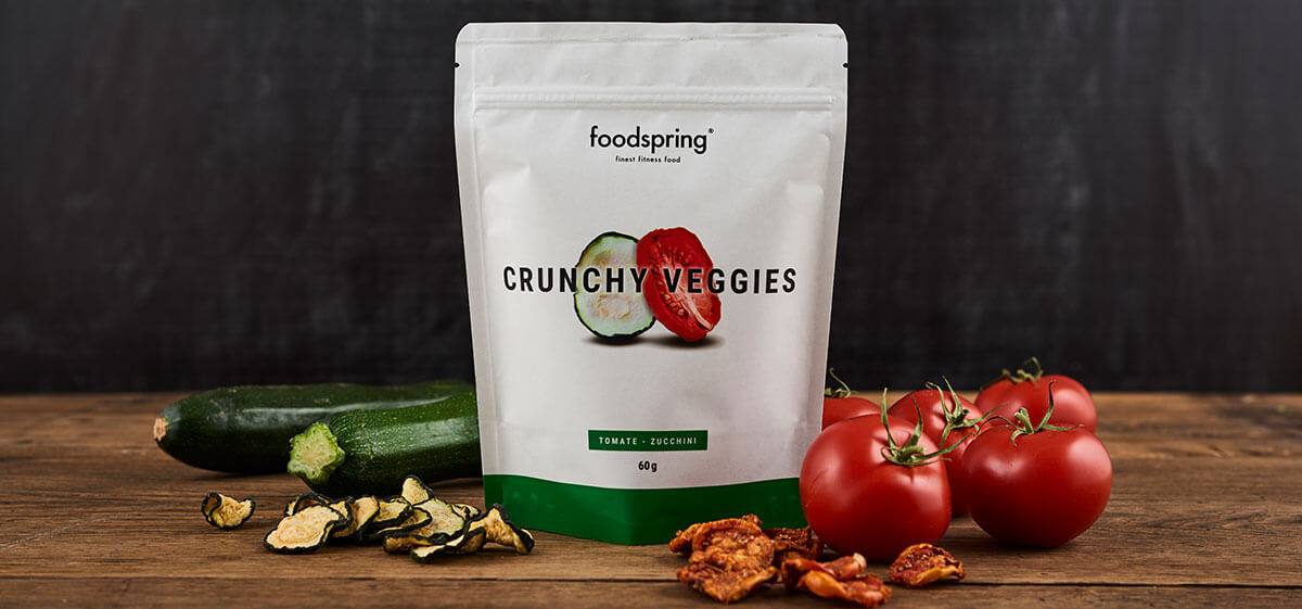 foodspring Crunchy Fruits Verpackung vor Zucchini und Tomaten