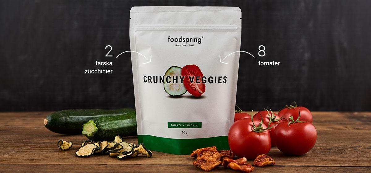 foodspring Crunchy Fruits förpackning framför squash och tomater