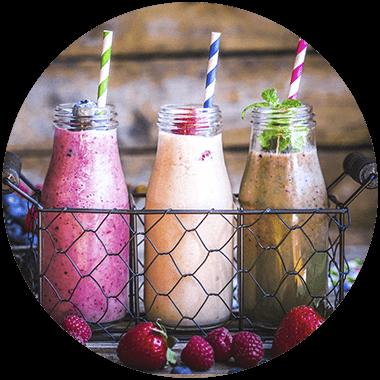 In Glasflaschen appetitlich angerichtete Shakes in drei Farben