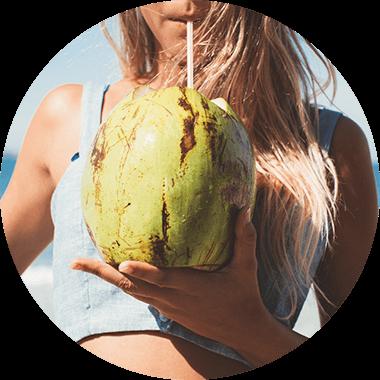 Una donna sportiva beve acqua di cocco